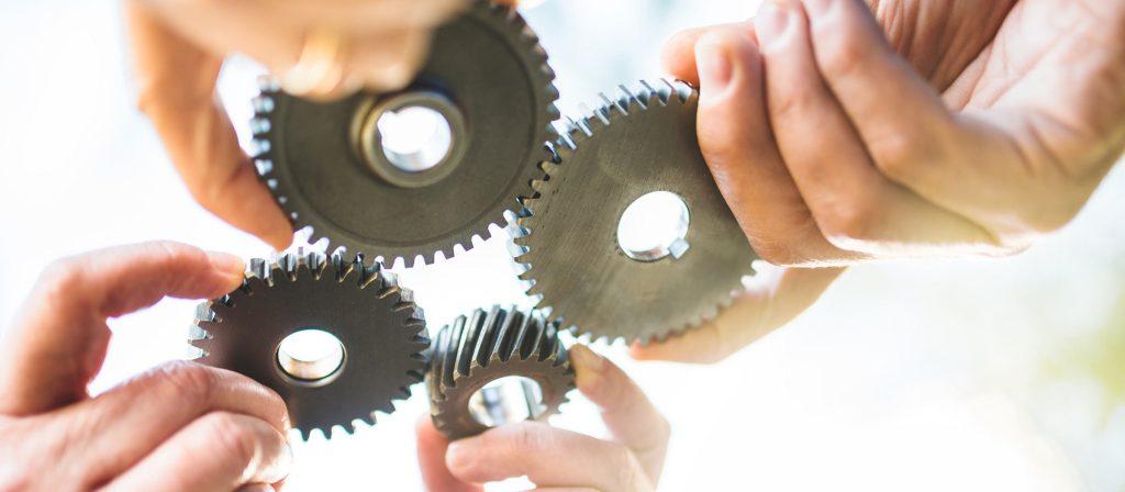 Zahnräder symbolisieren das Ineinandergreifen von Prozessen im Qualitätsmanagement
